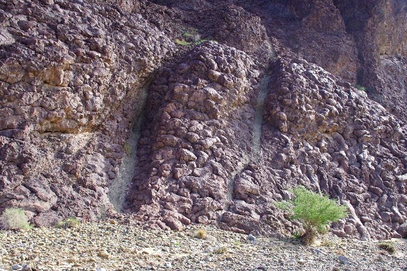Géotimes. Après la formation de l'amas de pilow-lavs, du magma est remonté formant ces dykes parallèles de couleur claire.