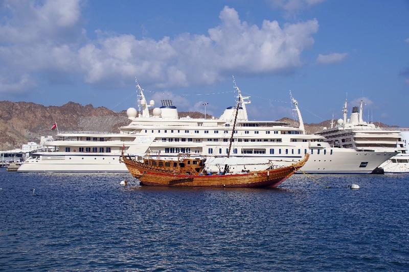 Au premier plan, un dhow (bateau traditionnel de pêche en bois) et juste derrière, Al Saïd, le yacht du sultan Qaboos ibn saïd.