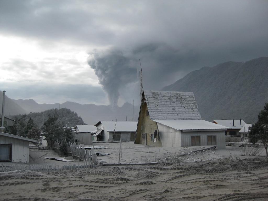 Vue le 26 juin 2008 de la ville de Chaitén évacuée et partiellement détruite par l'éruption du Chaitén visible au dernier plan. (Wikipédia)