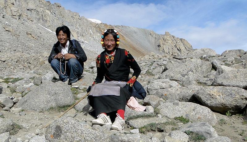 Un couple de tibétains. Le mari égraine son chapelet. Madame avec le tablier et la parure sur ses cheveux.