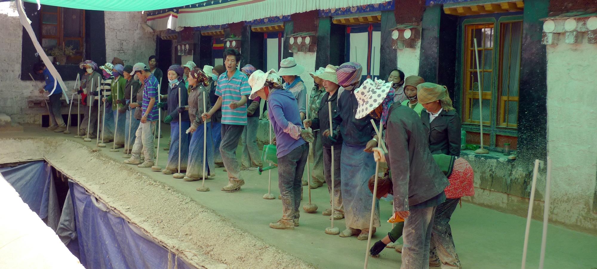 Groupe de jeunes tibétains refaisant le toit dans un monastère au rythme de leurs chants et martèlement de la pierre au bout du bâton.